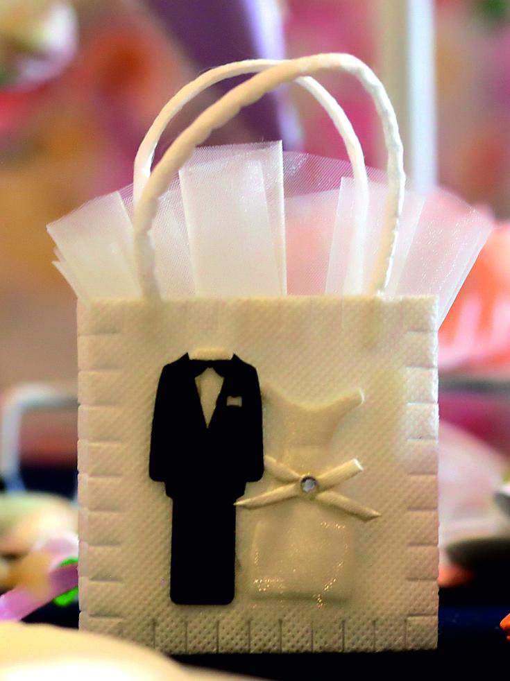 Сватбена торбичка в бял цвят с дръжки и фигури от плат на младоженци. В торбичката сме опаковали традиционен захарен бонбон в бяла тюлена кесийка, която се подава от торбата. Размери - височина с дръжката около 13 см; широчина 7,5 см; дебелина около 2,2 см. Срок за изработка: 10 работни дни. Минимално количество за поръчка: 50 броя. Цена за 1 брой: 1.60 лв.