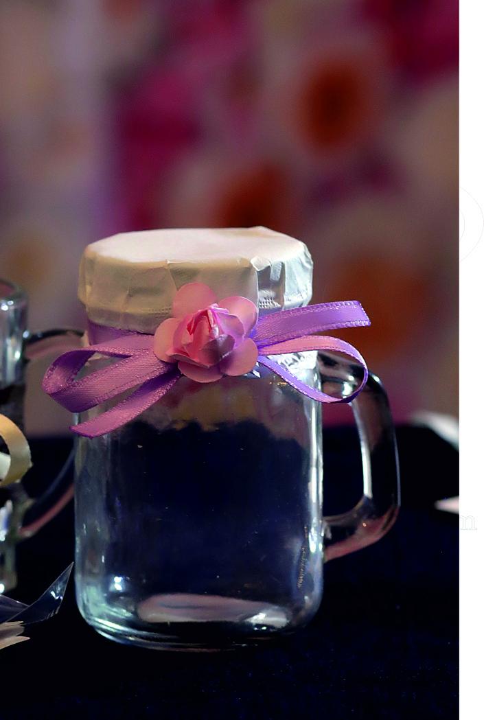Малко стъклено бурканче с дръжка и цветно капаче с отвор за сламка. Опаковано с фина хартия, сатенена панделка и цветче. По ваше желание цветовете на панделката и цветчето могат да бъдат други. Размери - височина 8,8 см; диаметър 5,6 см. Срок за изработка: 10 работни дни. Минимално количество за поръчка: 30 броя. Цена за 1 брой: 2.30 лв.