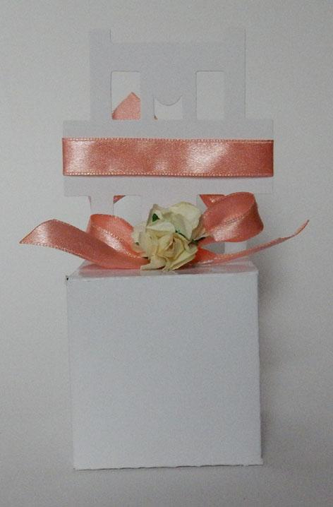 Подаръче - кутийка наподобяващо стол, във всяко едно има захарен бонбон. Опаковката е от плътен бял картон, декорирана със сатенени панделки и нежни хартиени цветчета. Кутийката е с горно и долно отваряне. По ваше желание панделките и цветчетата могат да бъдат в други цветове. Също така на всяко столче може да бъде написано името на госта срещу допълнително заплащане от 0.20 лв. за брой. Височина на столчето: 13,5 см. Размери на кутийката: 5,5 x 5,5 x 5,5 см. Минимално количество за поръчка: 50 броя. Цена за един брой: 2.80 лв.