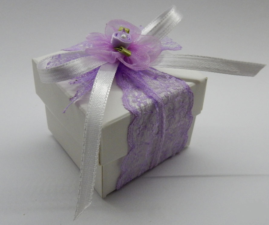 Картонена кутийка с капак за подаръчета за гости. Картона е в бял цвят, без допълнителни ефекти. В кутийката има бял захарен бонбон, а кутийката е запечатана с дантела в цвят по ваш избор, бели сатенени панделки, цветче и перлено мънисто. По ваше желание е възможно цветчето и дантелата да са в други цветове. Към кутийката има етикет с надпис по ваш избор. Размери - кутийка: 5,5 x 5,5 x 4,2 см; етикет: 4,5 x 2 см. Минимално количество: 30 броя. Цена за 1 брой: 1.70 лв.