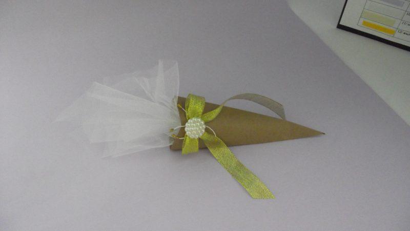 Декоративка опаковка, в която има цветен ризон, опакован с тюл. Изцяло ръчно направени от нас - картонена фунийка, декорирана с дантела в бял цвят, панделка и перлени мъниста. По ваше желание можем да добавим и етикет с текст по ваше желание с размер 5,5 x 8 см. Размери - дължина на картнената опаковка: 17 см.; най-широката част на опаковката: 7 см. Минимално количество за поръчка: 50 броя. Цена за 1 брой: 2.20 лв.