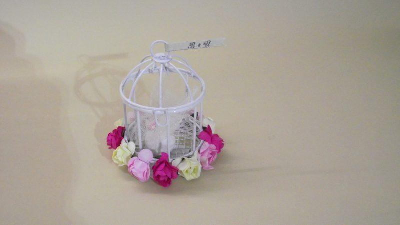 Метален мини кафез, декориран с нежни цветчета и малко етикетче с вашите инициали, поставен на върха на клетката. В кафеза има захарен бонбон, опакован в тюлена кесийка в бял цвят. По ваше желание е възможна промяна в цветовете на цветята в основата на кафеза. Размери: височина 8,7см; диаметър 6см. Етикет: дължина 4 см; дебелина 7 мм