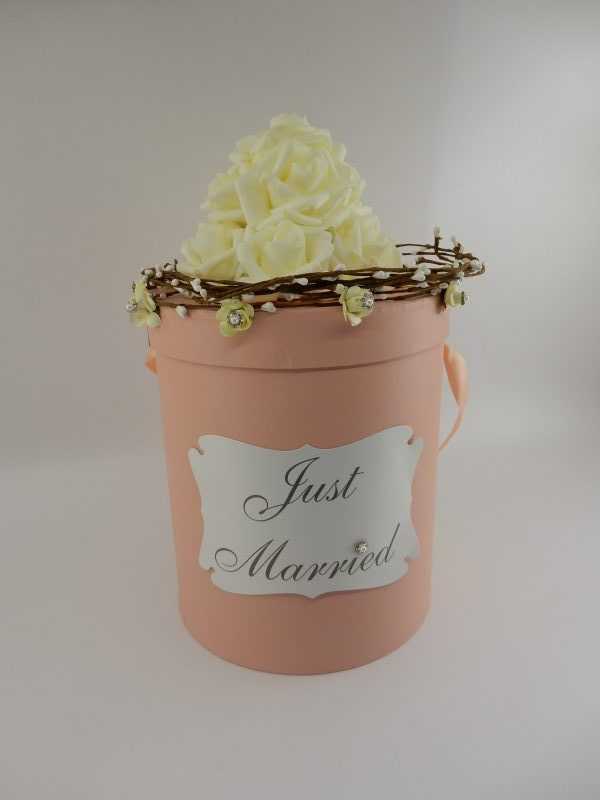 Кутия за пари с цилиндрична форма от дебел картон в цвят бледо розово (модерния цвят блъш). Декорацията е върху капака на кутията - букетче от силиконови рози в цвят шампанско и венче от декоративни сухи клонки с перли. Ръба на капака е украсен с малки цветове рози с по-малки цветя от блестящи перли и камъчета. На основното тяло на кутията сме поставили и табелка от бял перлен картон с надпис Just Married и цветче от камъчета и перла. Размери - височина с украсата31 см.; диаметър 20см. Кутията има и сатенена дръжка, отново в нежно розовия й цвят. Капака се отваря свободно, но няма допълнителен отвор. Ако желаете табелката да е с друг надпис моля, напишете ни текста. Това не би променило цената на кутията! Срок за изработка по договаряне. Цена за 1 брой: 55 лв.
