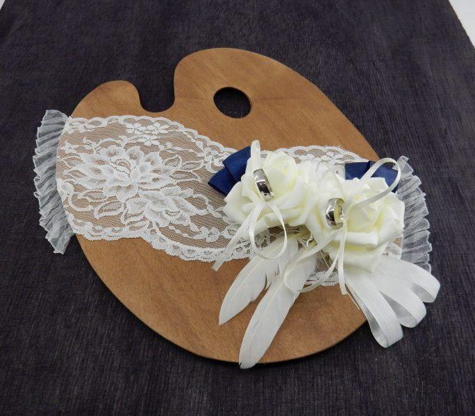 Дървена лека палитра с размери 30 / 23.5 см в тъмно кафяво,цвят орех. Дебелината на материала е 2 мм. С диагонално залепена бяла фина дантела. Пръстените се прикрепват с тънка бяла лента, всяка в силиконова роза в цвят шампанско. Двете рози са украсени с тъмно син, бял сатен, с две бели пера. * Пръстените в картинката не са включени в комплекта! * Срок за изработка по предварително договаряне. Цена за 1 брой: 28 лв.