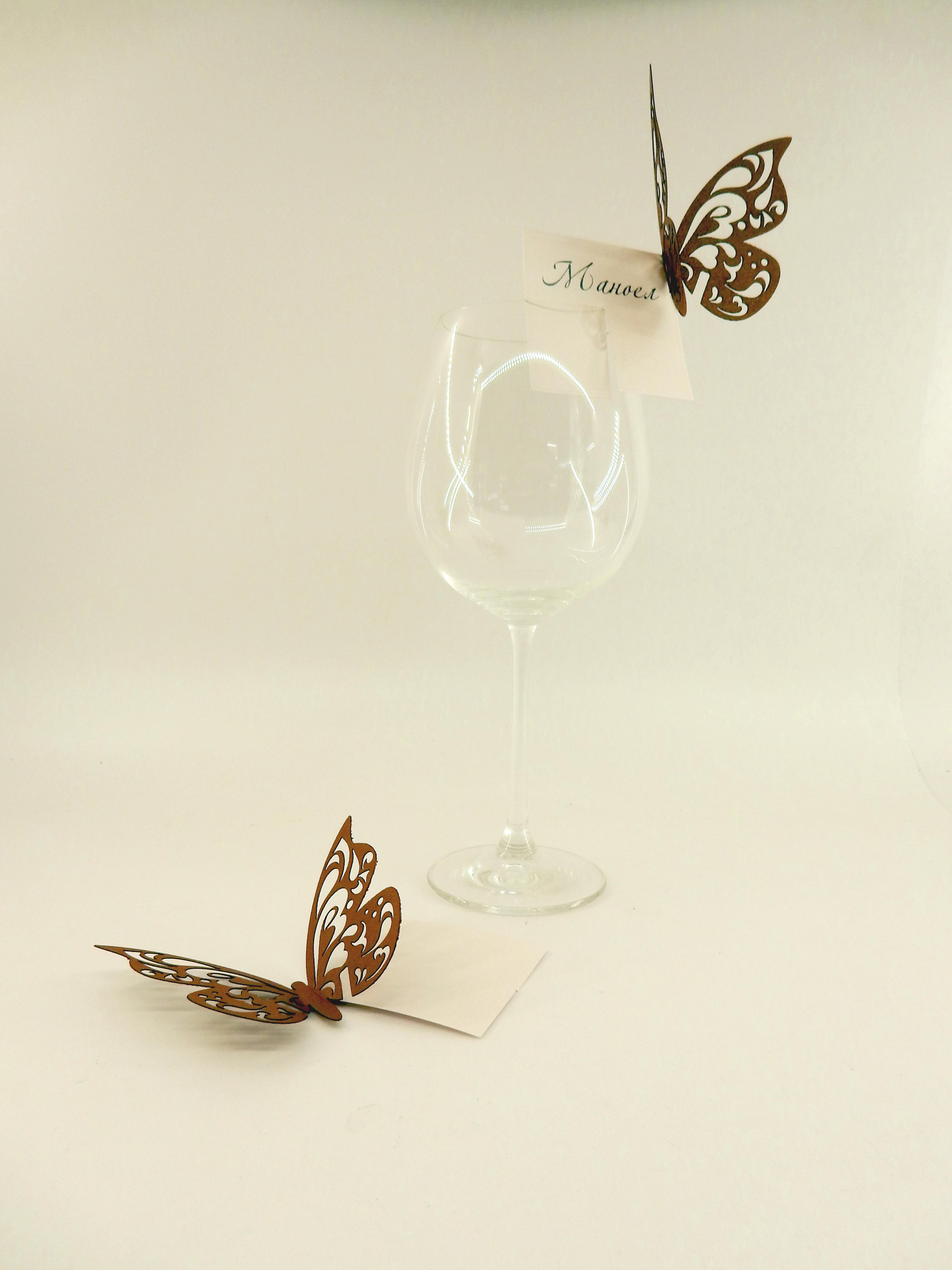 Елегантни табелки за имена за вашите гости декорирани с нежна пеперуда. Произведени от перлен картон в бяло и златисто кафяво, те са пригодени да бъдат закрепени на чаши. Ако желаете картона да е в друг цвят, свържете се с нас – ние ще се постараем поръчаната от вас декорация да е перфектна. Размери: Пеперуда - Най-дълга част: 7.5 см; Най- широка част: 12 см Табелка – 6.5 см x 6.5 см