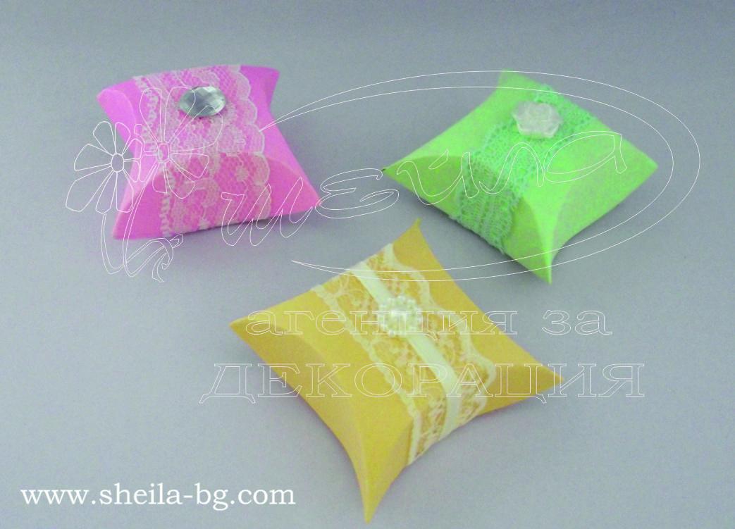 Ако желаете сами да направите подаръците за вашите гости, ние можем да ви съдействаме с елегантни опаковки! Ръчно направени от картон, декорирани с нежна дантела и деликатно перлено цветче или мънисто. За момента се предлагат в 3 цвята - зелено, оранжево и розово, но има възможност за още варианти при желание от вас. Кутийката е квадратна, в най- дългата си част е 5,5 см, а в най-тясната си част 3,5 см. Минимално количество за поръчка: 50 броя. Цена за 1 брой: 1.00 лв.