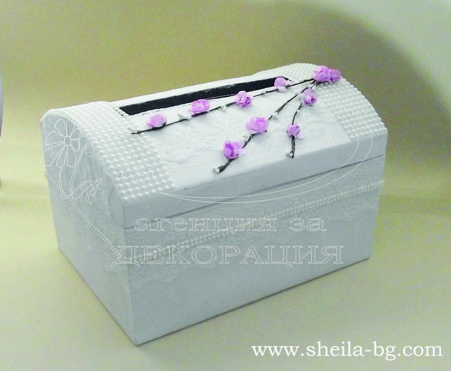 Кутия за пари от дебел картон, облечена допълнително с бял перлен и релефен картон. Декорацията е от фина бяла дантела, перли в цвят бледо шампанско и декоративни клонки с нежни розови цветове. Размери на кутията - дължина 30 см, височина 21 см, ширина 21см. Капака на кутията има отвор за пликове с размери - 20 x 3 см. Освен това, че има отвор в капака, самия капак е функционален, т.е. може да се отваря и затваря свободно. Срок за изработка по договаряне. Цена за 1 брой: 48.00 лв