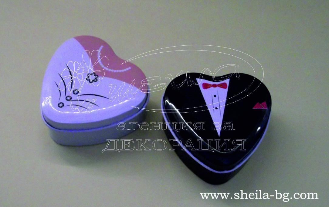 Метални кутийки във формата на сърце, пълни с цветен ризон. С тематична визия - булка и младоженец. Размери - в най-широката/дългата част: 7 x 7,5 см; височина: 3,5 см. Минимално количество за поръчка: 10 броя. Цена за 1 кутийка пълна с шепа цветен ризон: 1.60 лв.