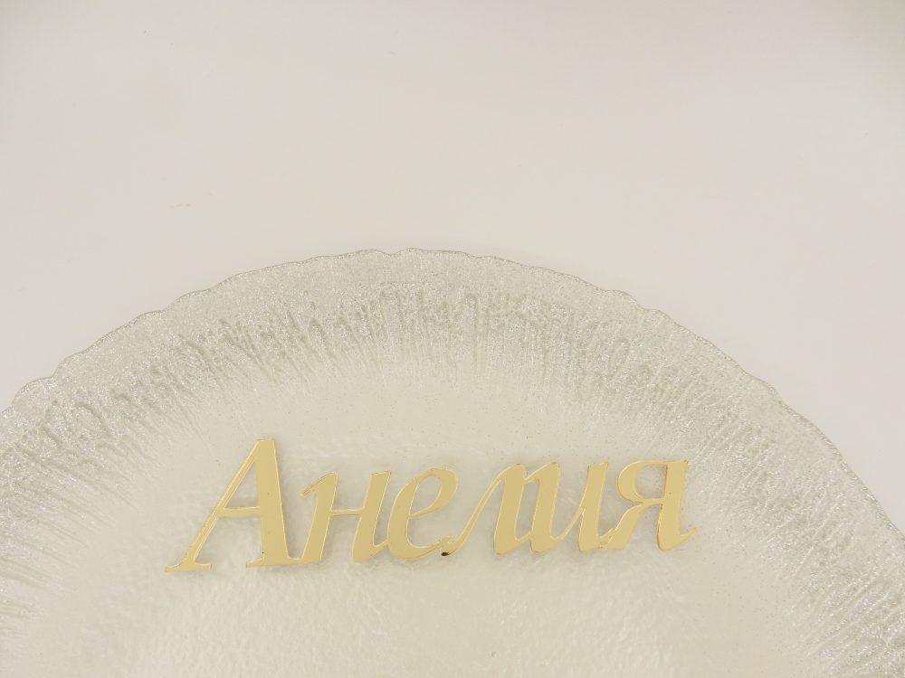 Лазерно изрязани имена от златен огледален плексиглас за обозначаване местата на гостите. Тези персонализирани табелки са идеалния завършек на стилна декорация. Поставете го в чинията или на масата, вместо обикновената картичка с имената, за да могат гостите да намерят местата си. След събитието гостите могат да ги запазят като елегантен подарък за спомен. Материалът може да бъде златен или сребърен. Размери: Височина на най-голямата буква: 4 см Дебелина: 2мм Дължина: зависи от броя букви на името. Предлагаме два вида шрифтове! Срок за изработка: 10 работни дни. Цена за брой: 2.50 лв(при минимално количество 20 броя)