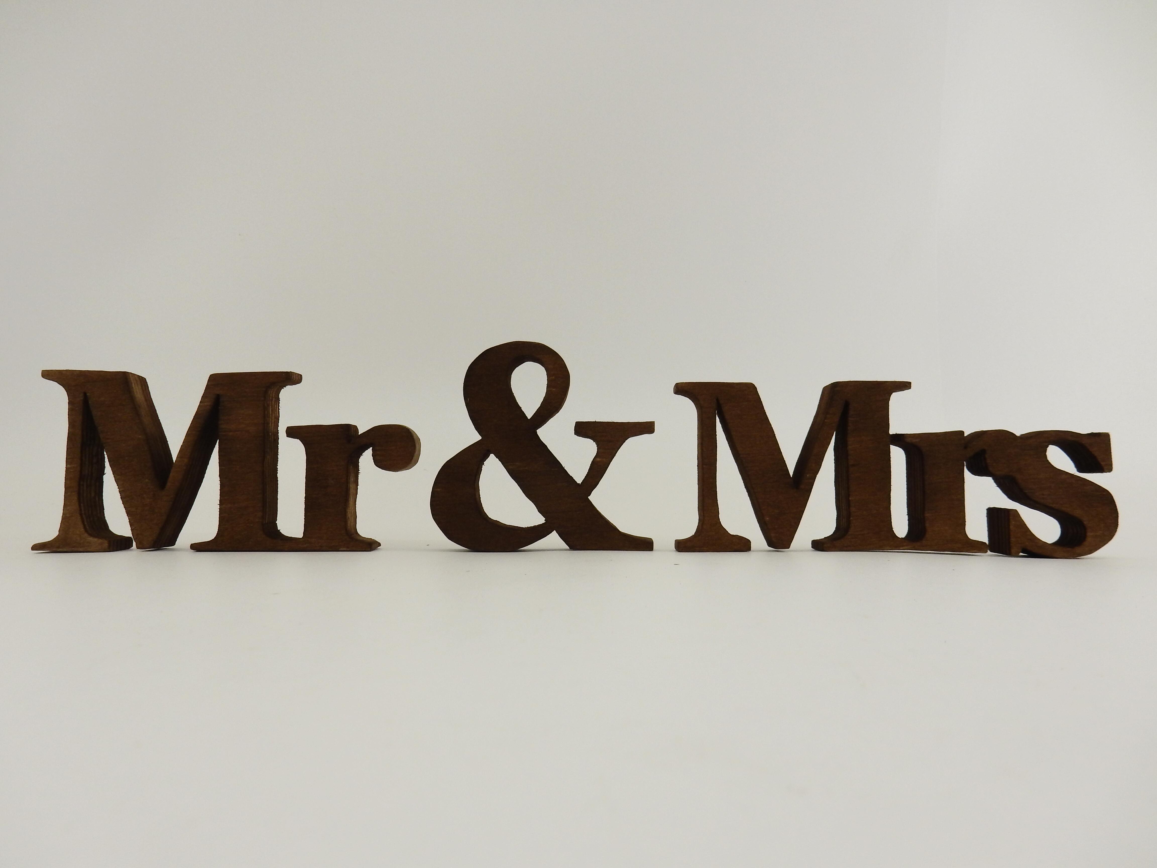 Надпис Mr & Mrs ръчно изработен от брезов шперплат. Идеален като семпъл акцент към декорацията на младоженската маса, надписа би могъл да бъде декор към вашата сватбена фотосесия. Декорация, която ще остане скъп спомен и ще краси вашия дом. Материалът е обработен с байц. Размери- дебелина на буквите: 1,8 см; височина- голяма буква: 6.5см; малка буква: 5.8см. Дължина- Mr: 13 см; Mrs : 17 см. Знак & - 8.5 x 8.7 см.